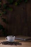 Tazza di caffè e chicchi di caffè su di legno Fotografia Stock