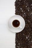 Tazza di caffè e chicchi di caffè su priorità bassa bianca Immagine Stock Libera da Diritti