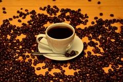 Tazza di caffè e chicchi di caffè sulla tavola di legno Fotografia Stock Libera da Diritti