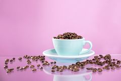 Tazza di caff? e chicchi di caff? sul fondo di colore immagine stock