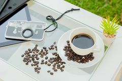 Tazza di caffè e chicco di caffè sullo scrittorio con gadge fotografie stock libere da diritti