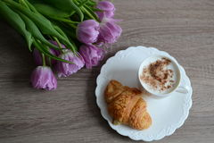 Tazza di caffè e croissant squisiti con i fiori Immagini Stock