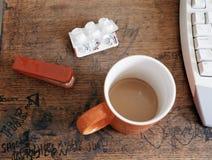 Tazza di caffè e dei graffiti sullo scrittorio Fotografia Stock