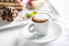 Tazza di caffè e dessert sul piatto nei confettieri del caffè o nella ricerca fotografie stock