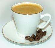 Tazza di caffè e fagioli su un piattino immagini stock libere da diritti