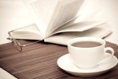 Tazza di caffè e libro bianchi con i vetri Immagini Stock