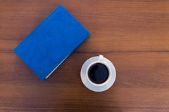 Tazza di caffè e mistero sulla tavola di legno fotografia stock