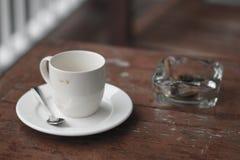 Tazza di caffè e portacenere vuoti fotografie stock
