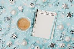 Tazza di caffè e taccuino con per fare lista sulla vista superiore del fondo blu concetto di pianificazione di natale Disposizion Immagine Stock