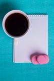 Tazza di caffè e tre maccheroni rosa, taccuino Fotografia Stock