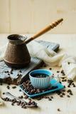 Tazza di caffè e Turco del metallo sul fondo della tela da imballaggio Immagini Stock