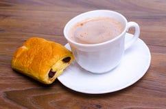 Tazza di caffè e un dolce sulla tavola in caffè Immagine Stock