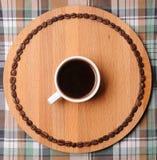 Tazza di caffè espresso sul bordo di legno rotondo con il circuito dei chicchi di caffè Sul fondo del plaid Immagini Stock
