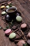 Tazza di caffè, fagioli, cioccolato e maccheroni di colore sulla tavola Immagini Stock