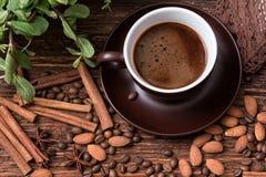 Tazza di caffè, fagioli, mandorla e cannella sul vecchio tavolo da cucina Fotografie Stock