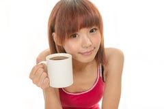 Tazza di caffè femminile asiatica della tenuta Fotografie Stock Libere da Diritti