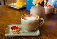 Tazza di caffè, forma del cuore con il biscotto della fragola su legno Immagini Stock Libere da Diritti