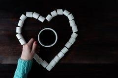 Tazza di caffè fra le caramelle gommosa e molle nella forma di cuore su dar di legno Fotografia Stock