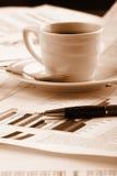 Tazza di caffè fragrante su un commercio del documento di mattina immagini stock