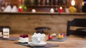Tazza di caffè fresca accanto alle torte ed ai dolci dolci archivi video