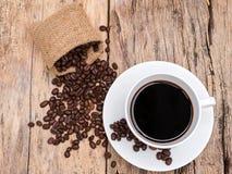 Tazza di caffè fresca del caffè espresso con il chicco di caffè sulla tavola di legno Fotografia Stock Libera da Diritti