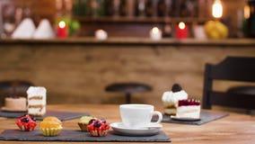 Tazza di caffè fresco accanto alle torte di frutta su una banda nera video d archivio