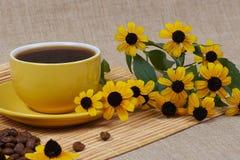 Tazza di caffè gialla con i fiori Immagine Stock