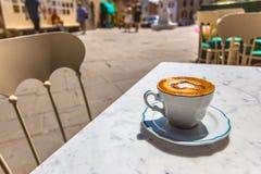 Tazza di caffè italiana ad un terrazzo con la vista della via, Italia del caffè Fotografie Stock Libere da Diritti