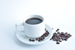 tazza di caffè macchiato e chicco di caffè su fondo bianco fotografia stock
