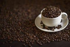 Tazza di caffè macchiato in pieno dei chicchi di caffè arrostiti e dei chicchi di caffè arrostiti sulla tavola di legno Immagini Stock