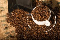 Tazza di caffè macchiato in pieno dei fagioli, bordi da più chicchi di caffè Fotografie Stock Libere da Diritti
