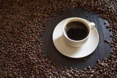 Tazza di caffè macchiato in pieno di caffè e dei chicchi di caffè arrostiti sui chicchi di caffè di legno della tavola vicino su  Fotografia Stock