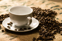 Tazza di caffè macchiato su un sacco del caffè con i semi di cacao torrefatti intorno Fotografia Stock Libera da Diritti