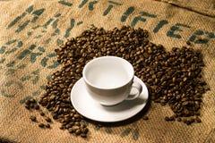 Tazza di caffè macchiato su un sacco del caffè con i semi di cacao torrefatti intorno Immagine Stock Libera da Diritti