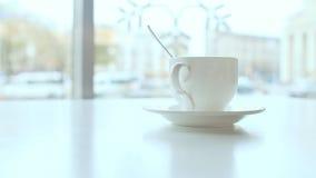 Tazza di caffè macchiato sulla tavola in caffè contro una finestra del fondo archivi video