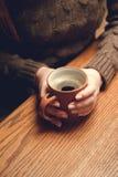 Tazza di caffè in mani femminili Immagine Stock