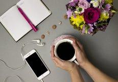 Tazza di caffè, mazzo dei fiori, taccuino fotografia stock libera da diritti