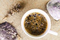 Tazza di caffè messa in sabbia alla spiaggia Immagine Stock