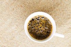 Tazza di caffè messa in sabbia alla spiaggia Immagini Stock