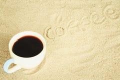 Tazza di caffè messa in sabbia alla spiaggia Immagine Stock Libera da Diritti