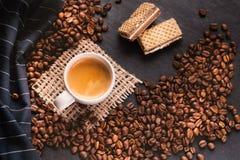 Tazza di caffè in mezzo ai chicchi di caffè con i biscotti e la tovaglia Prodotto granuloso Bevanda calda Fine in su Raccolta Nat fotografie stock libere da diritti