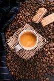 Tazza di caffè in mezzo ai chicchi di caffè con i biscotti e la tovaglia Prodotto granuloso Bevanda calda Fine in su Raccolta Nat immagini stock
