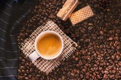 Tazza di caffè in mezzo ai chicchi di caffè con i biscotti e la tovaglia Prodotto granuloso Bevanda calda Fine in su Raccolta Nat immagini stock libere da diritti