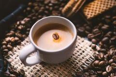 Tazza di caffè in mezzo ai chicchi di caffè con i biscotti e la tovaglia Prodotto granuloso Bevanda calda Fine in su Raccolta Nat fotografie stock