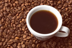 Tazza di caffè nei chicchi di caffè Immagini Stock
