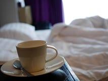 Tazza di caffè nella camera da letto con il fondo della sfuocatura fotografia stock libera da diritti