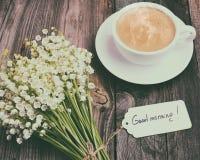 Tazza di caffè nero caldo e un mazzo dei gigli freschi del val Fotografia Stock