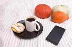 Tazza di caffè nero con Donato con la glassa bianca e lo stri giallo Fotografia Stock Libera da Diritti