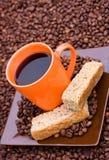 Tazza di caffè nero con i fagioli e le fette biscottate Immagine Stock