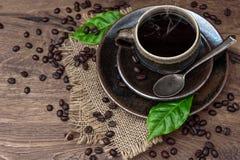 Tazza di caffè nero con i fagioli e le foglie Immagine Stock